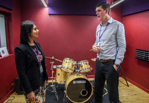 Picture of Sara Khan talking to a Poplar HARCA employee, standing in front of a drum kit